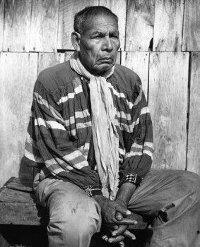 Seminole man sitting with his hands clasped, 1970s