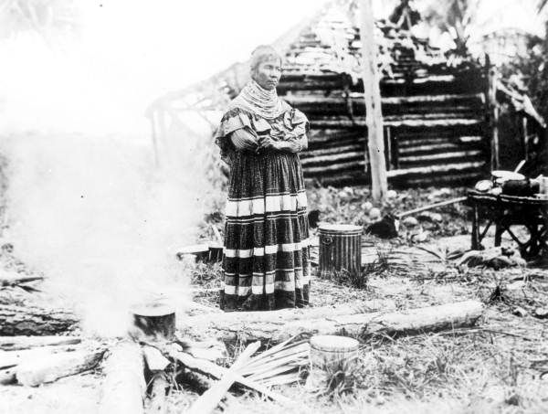 Seminole woman at cooking fire beside log cabin