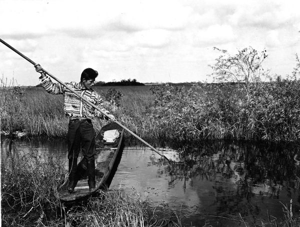 Tommy Tiger gigging from a dugout canoe in the Everglades 1950